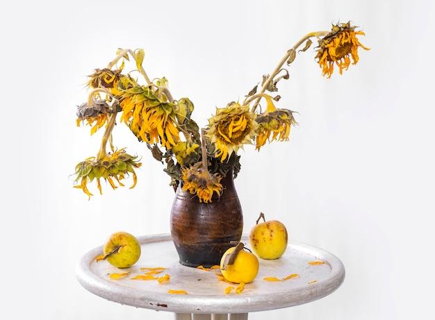 Trockener strauß sonnenblumen in vase und äpfel auf dem tisch. herbststillleben