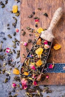 Trockener tee auf basis von grün mit früchten und rosenblättern