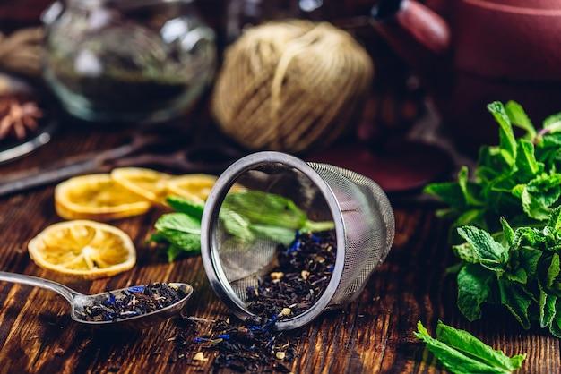 Trockener tee in sieb und löffel mit frischem minzbündel und zitronenscheiben. gewirr mit zwei gläsern und teekanne auf hintergrund.