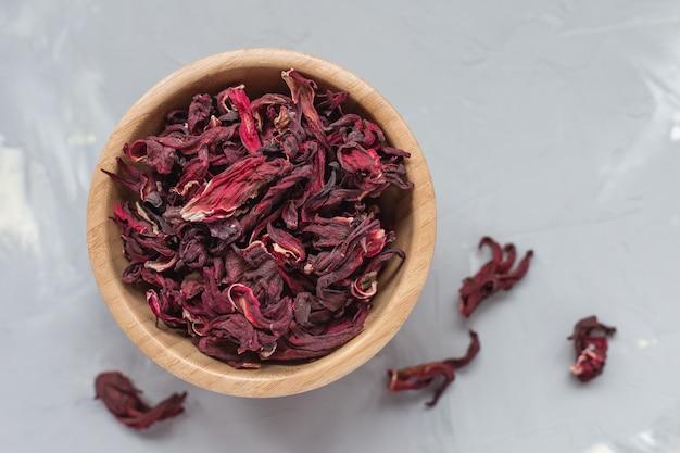Trockener tee von roten hibiskusblättern, auch bekannt als karkade- oder roselle-frucht, in der holzschale auf, konzept des gesunden getränks. nahaufnahme, selektiver fokus, kopierraum