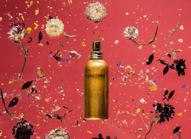 Trockenes bellis-kraut mit blumen und parfümflasche auf rotem hintergrund lokalisiert. ohne schatten