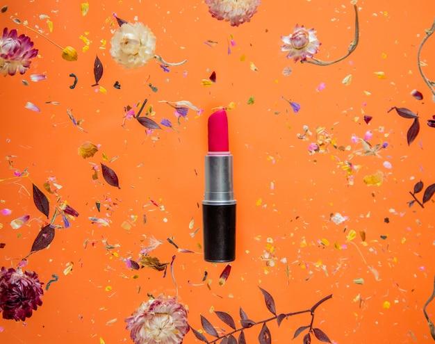 Trockenes bellis kraut mit blumen und rotem lippenstift auf orange hintergrund lokalisiert. ohne schatten