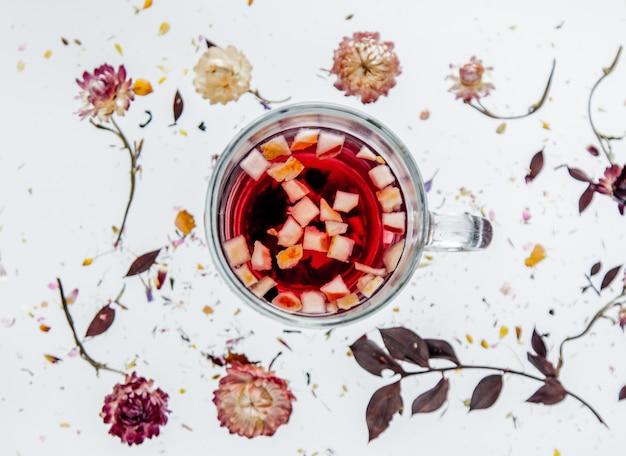 Trockenes bellis-kraut mit blumen und tasse tee auf grauem hintergrund lokalisiert. ohne schatten