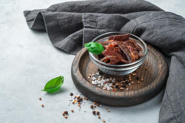 Trockenes fleisch auf einer holzplatte mit gewürzen, salz und basilikum an einer grauen wand. seitenansicht mit kopienraum.
