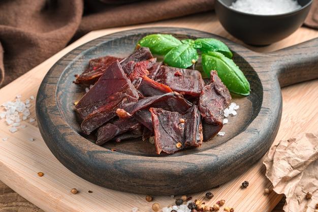Trockenes fleisch nahaufnahme mit salz und pfeffer auf einem hellen holzbrett.