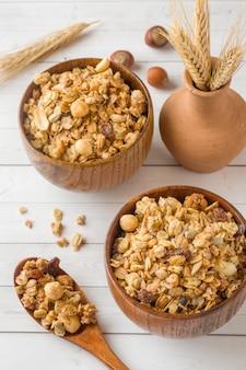 Trockenes frühstück mit haferflocken, granulat und nüssen. müsli in einer tiefen holzplatte.
