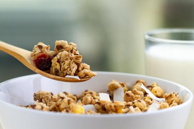 Trockenes frühstückszerealien. knusprige honig-müslischüssel mit leinsamen, moosbeeren, kokosnuss und einem glas milch nah oben. gesundes, sauberes und ballaststoffreiches essen. frühstückszeit