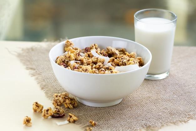 Trockenes frühstückszerealien. knusprige honigmüslischüssel mit leinsamen, moosbeeren und kokosnuss und einem glas milch auf einer tabelle. gesundes und ballaststoffreiches essen. frühstückszeit