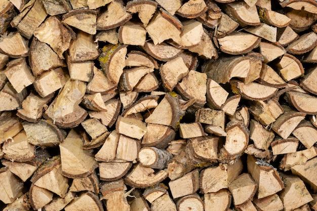 Trockenes gehacktes brennholz meldet einen stapel an, der zum winter bereit ist