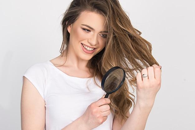 Trockenes geschädigtes haar, haarpflege, trockene enden, haarschnittkonzept. junges mädchen hält ihr haar und schaut durch die lupe, die die qualität prüft.
