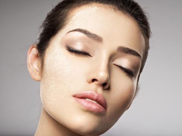 Trockenes kosmetisches make-up-puder ist auf dem weiblichen gesicht. schönheitsbehandlungskonzept. mädchen macht make-up.