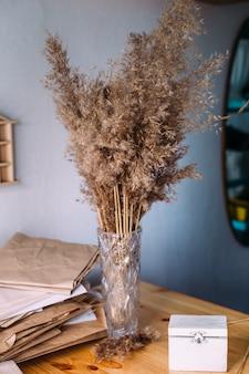 Trockenes schilf schilf in vase bastelpapier holz und neutrale farben in stillleben