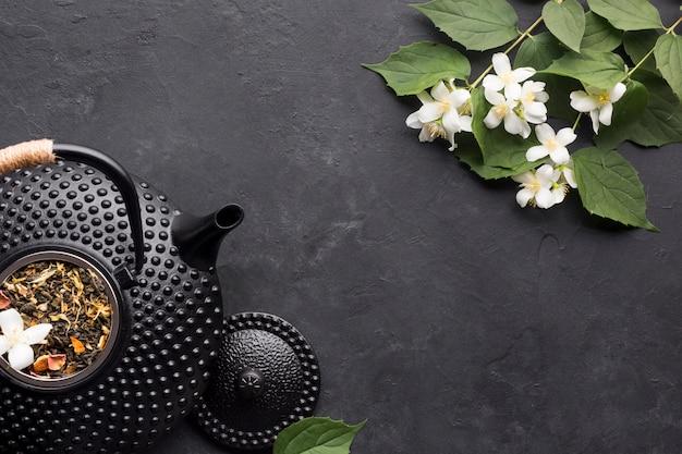 Trockenes teekraut mit frischer weißer jasminblume auf dem schwarzen gemasert
