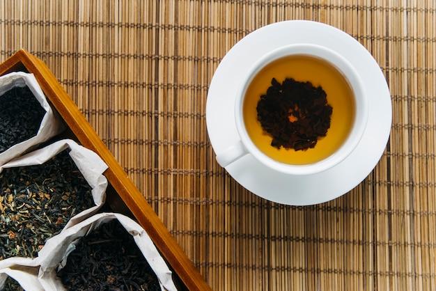 Trockenes teekraut mit kräutertee auf tischset