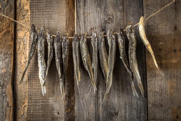 Trockenfisch, der an einer linie auf alten brettern hängt