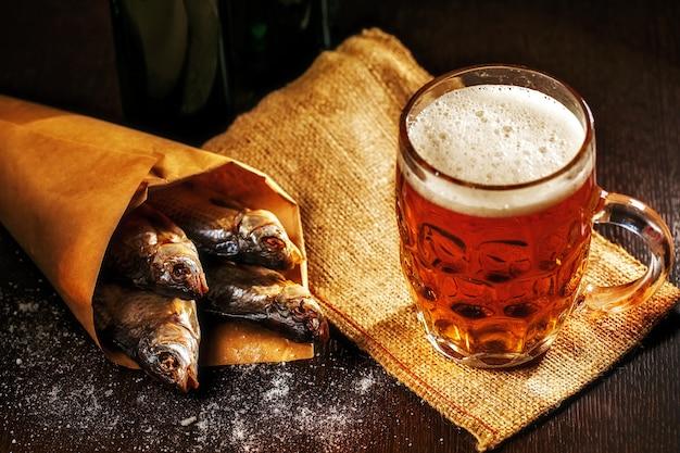 Trockenfisch- und weinleseglas bier auf dunklem holztisch