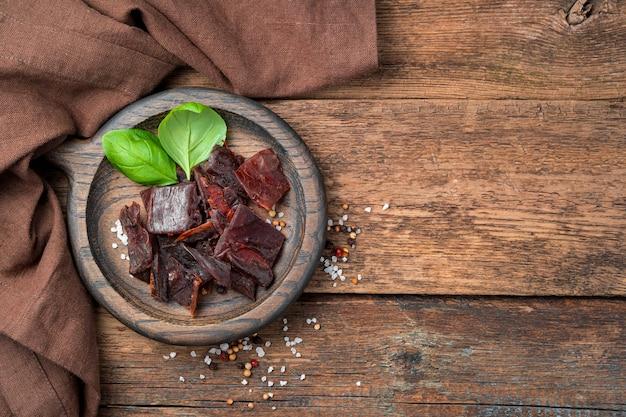 Trockenfleisch, basilikum und gewürze auf braunem holzhintergrund