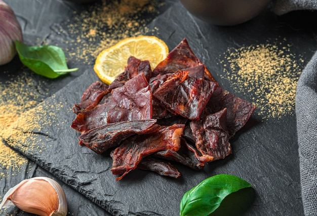 Trockenfleisch vom rind an einer schwarzen wand mit gewürzen und zitrone. seitenansicht, nahaufnahme.