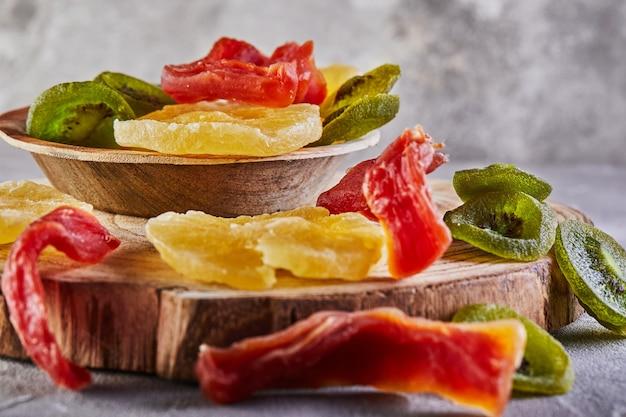 Trockenfrüchte: gelbe kandierte ananasringe, rote papaya und grüne kiwi auf einem holzbrett und in einem holzteller