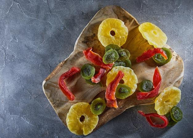 Trockenfrüchte: gelbe kandierte ananasringe, rote papaya und grüne kiwi auf einem holzschneidebrett auf grauem beton