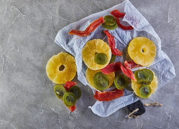 Trockenfrüchte: gelbe kandierte ananasringe, rote papaya und grüne kiwi auf weißem geschenkpapier auf grauem beton