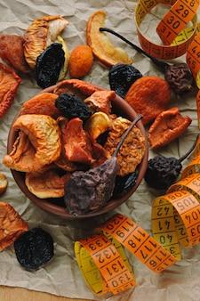 Trockenfrüchte in einer schüssel und maßband. konzept der getrockneten früchte für einen schlanken körper.