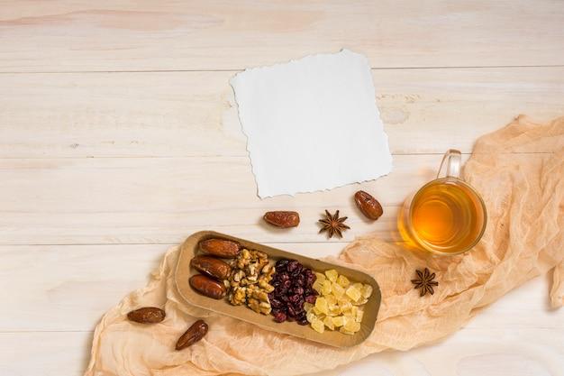 Trockenfrüchte mit walnüssen, papier und tee