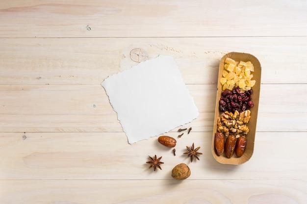 Trockenfrüchte mit walnüssen und blatt des leeren papiers