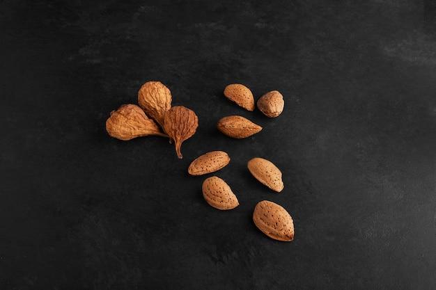 Trockenfrüchte und nüsse auf schwarzem backgorund.