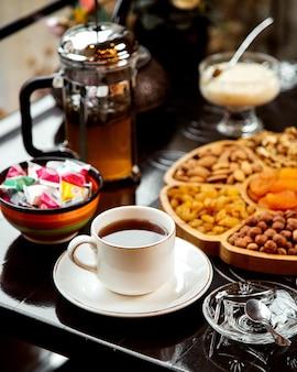Trockenfrüchte und nüsse mit tee und süßigkeiten