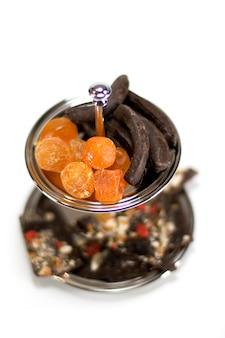 Trockenfrüchte und schokolade in einer schüssel lokalisiert auf weißem hintergrund
