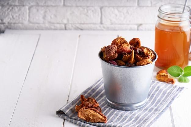 Trockenfrüchte und selbst gemachtes kompott von trockenfrüchten in einem glas auf einem leuchtpult.
