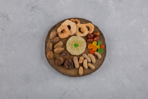 Trockenfrüchte und snacks in holzplatte in der mitte