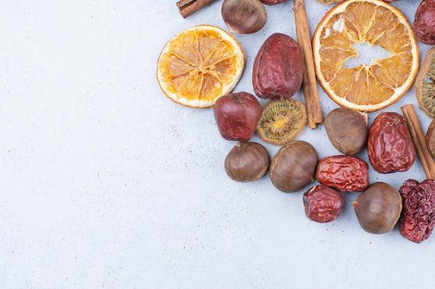 Trockenfrüchte, zimtstangen und kastanien auf marmoroberfläche.