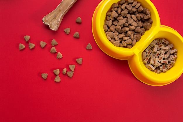 Trockenfutter für haustiere in schüssel auf rotem hintergrund draufsicht. stillleben. platz kopieren