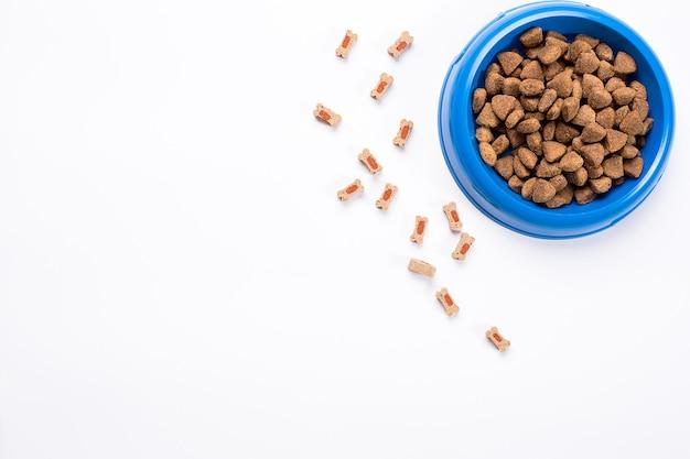 Trockenfutter für haustiere in schüssel auf weißem hintergrund draufsicht