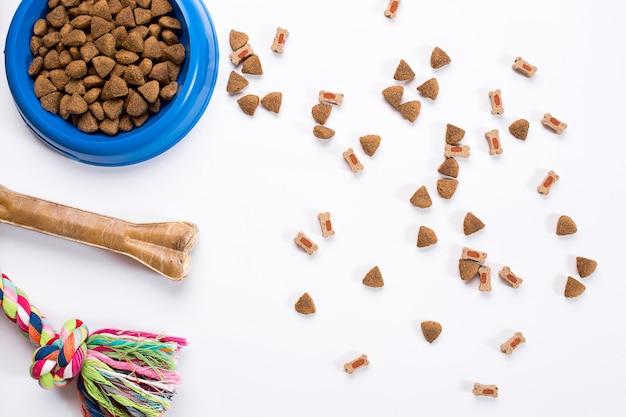 Trockenfutter für haustiere in schüssel und spielzeug für hunde auf weißem hintergrund draufsicht
