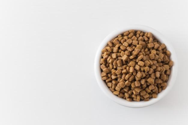 Trockenfutter für katzen oder hunde in einer weißen schüssel auf einem weißen hintergrund. ansicht von oben.
