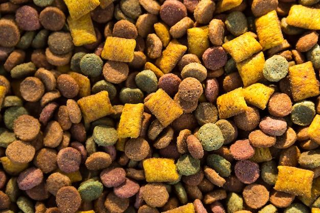Trockenfutter für katzen und hunde aus nächster nähe - ein hintergrund aus runden pellets und kissen mit weicher füllung. gesunde tiernahrung, exemplar
