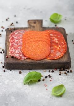 Trockengehärtete chorizo-wurstscheiben mit peperoni und salami mit basilikum und pfeffer