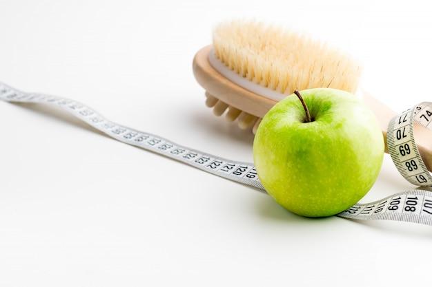 Trockenmassagebürste mit maßband und einzelnem grünem apfel auf weißem schreibtisch. gesundheit und diät.