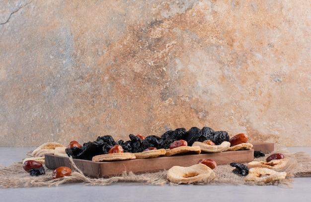 Trockenobstplatte mit apfelscheiben, rosinen und kirschen.
