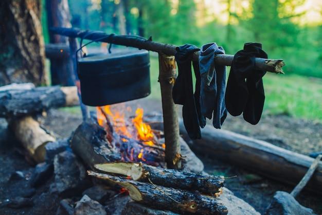 Trocknen nasser kleidung auf dem lagerfeuer während des campings. socken auf feuer trocknen. kessel und wasserkocher über dem lagerfeuer. kochen von lebensmitteln auf die natur. brennholz und zweige in brand. aktive erholung im wald.