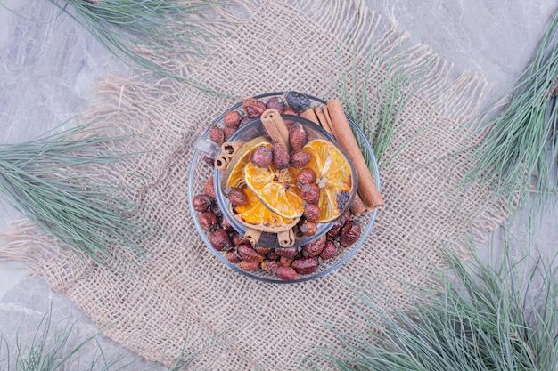Trocknen sie orangenscheiben und hüften mit zimtstangen in einer glasschale
