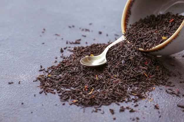 Trocknen sie schwarze teeblätter mit schüssel und löffel auf dunkel