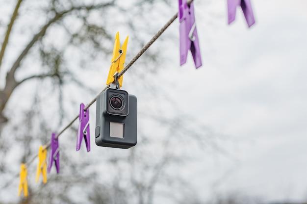 Trocknende wasserdichte action-kamera auf wäscheklammern, gegen den himmel.
