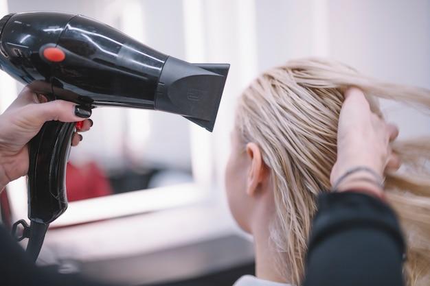 Trocknendes haar des anonymen friseurs