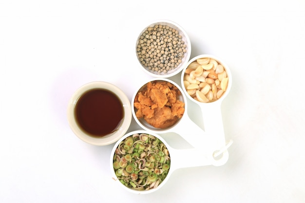 Trocknet paprikas, pfeffer, zitronengras, knoblauch, kokosnusszucker und fischsauce, thailändische kräuter auf weiß.