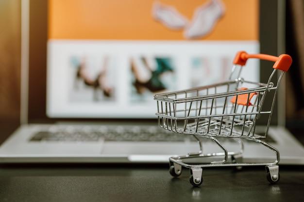 Trolley einkaufswagen mit computer laptop auf einem tisch. konzept für online-einkäufe oder e-commerce über das internet zum schutz vor coronavirus covid-19