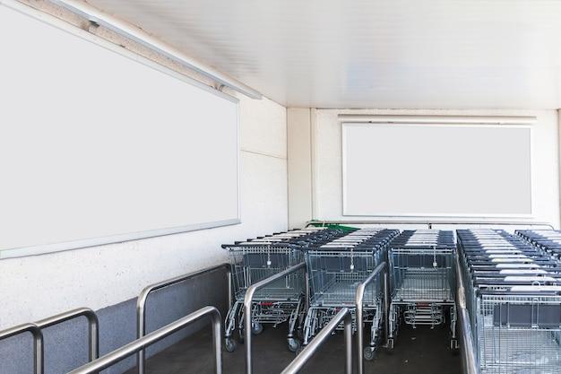Trolleysgepäck im einkaufszentrum mit leeren anschlagtafeln für anzeige